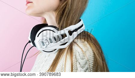 Young Woman In A Sweater With White Headphones. Musical Headphones.