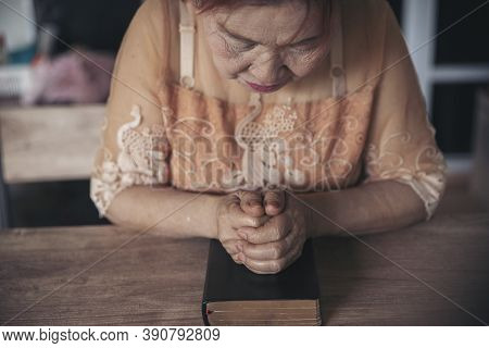 Prayer And Bible Concept. Asian Senior Woman Praying, Hope For Peace The World And Free From Coronav