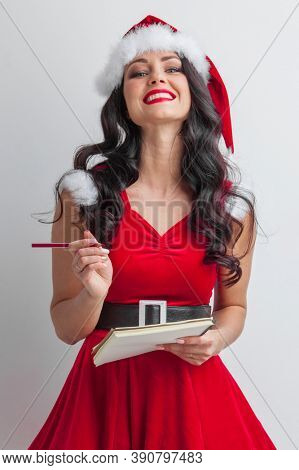 Pretty smiling pin-up Santa girl with wish list letter and red pencil