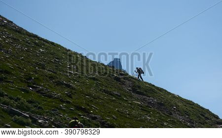Silhouette Of Mountaineer With Trekking Sticks Ascending Rocky Mountain. Traveler With Backpack Walk