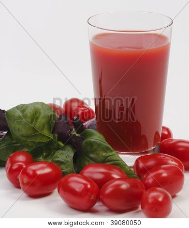 Glass of juice with tomato and basil