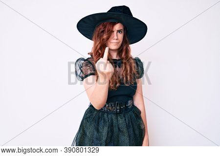 Young beautiful woman wearing witch halloween costume showing middle finger, impolite and rude fuck off expression