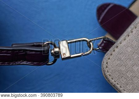 Red Leather Harness With A Yellow Metal Snap Hook On A Gray Bag On A Blue Background