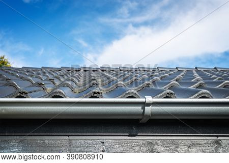 Roof On A House With Tiles And A Gutter. Clean Rooftop Under A Blue Sky.