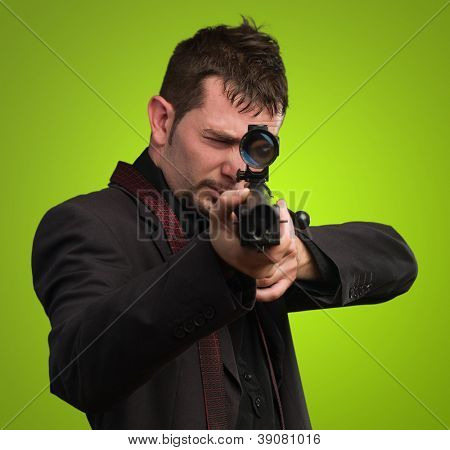 Man aiming with rifle against a green background