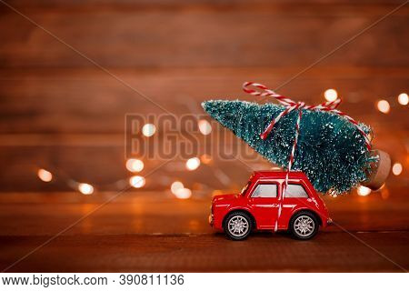 Miniature Red Car Toy Delivering Christmas Tree On Wooden Background With Light. Christmas Greeting
