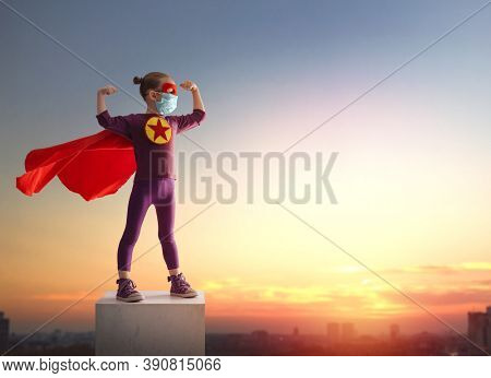 Little child playing superhero and wearing face mask during coronavirus and flu outbreak. Virus and illness protection, quarantine. COVID-2019. Kid on the background of sunset sky.