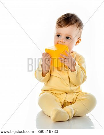 Little Cute Baby Child Gnawing Toy Chewing Yellow Block Cube Sitting On Floor. Ecological Hygienic H