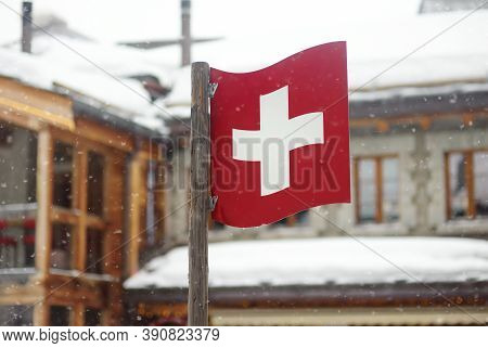 National Swiss Flag  On Street Of Small Town In Alps, Switzerland With Chalet On Background. Winter