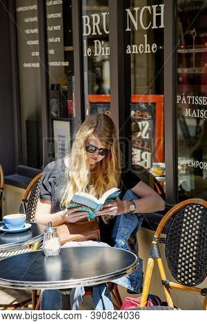 France, Bordeaux, May, 19, 2019 - Young Woman Reading Romance In Paper Book On An Open Veranda In A
