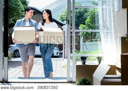 Asian Couple, Husband And Attractive Wife Helping Each Other To Lift The Box Happily, To Move Into A