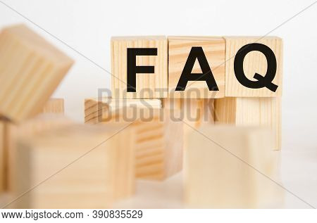 Wooden Blocks With The Word Faq On A White Table. In The Foreground Cubes In A Blurred Background. F