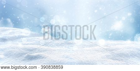 Winter Snow Background With Snowdrifts. Snowy Landscape With Beautiful Bokeh Lights And Snow Flakes.