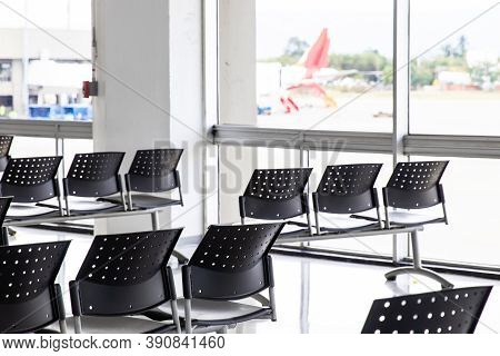 Empty Waiting Room At An Airport During Covid-19 Pandemic With Social Distancing Signs On Chairs