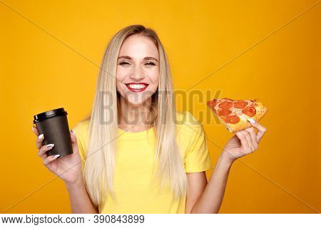 Happy Woman Eating Pizza And Holding A Cup Of Coffee Isolated Over The Yellow Background.