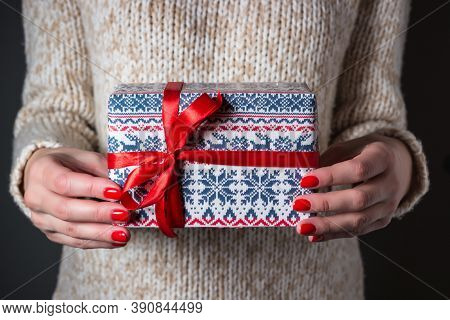 Woman In A Light Sweater Holding Christmas Present. Gift Delivery Concept