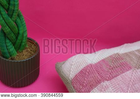Decorative Knitted Pillow With A Home Plant On A Pink Background. Home Decor