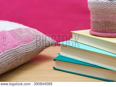 Old Books On A Wooden Shelf Pink Background And Knitted Decorative Pillow. Home Decor