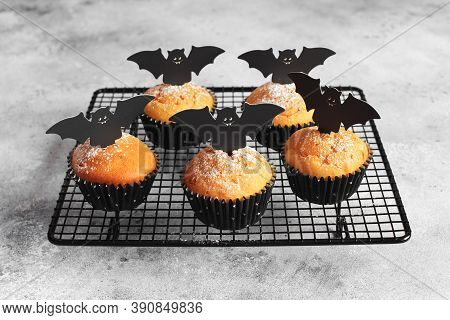 Halloween Pumpkin Muffins In Black Capsules Decorated With Cardboard Bats. Festive Halloween Cupcake