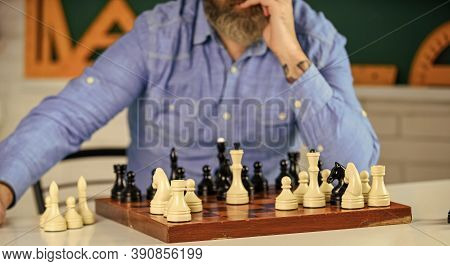 Tournament Skills. Chess Figures On Wooden Board. Focused School Teacher. Thinking Of Attacking And
