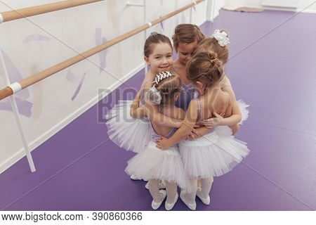 Top View Shot Of A Group Of Cute Little Ballrinas Wearing Violet Leotards And Tutus Hugging Together