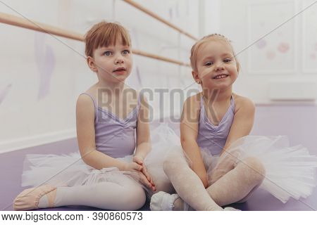 Cute Happy Little Girl Wearing Leotard And Tutu Skirs Smiling To The Camera Sitting With Her Friend