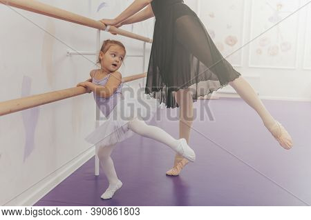 Graceful Ballerina Teaching Ballet To Adorable Little Girl In Tutu And Leotard. Cute Little Girl Enj