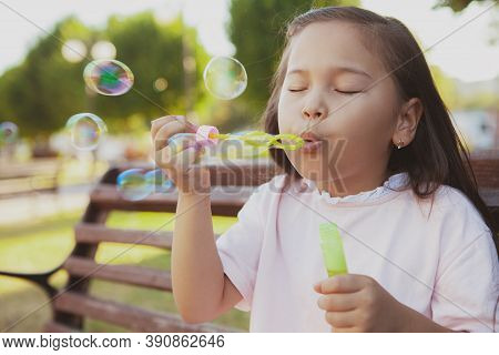Close Up Of A Cute Little Asian Girl Having Fun Outdoors In The Park, Blowing Bubbles. Adorable Chil