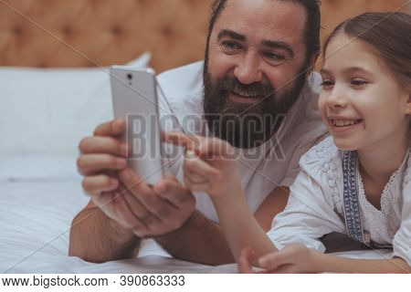Cropped Close Up Of A Beautiful Cheerful Little Girl Browsing Online, Using Smart Phone With Her Lov
