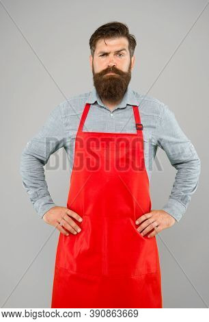 Bearded Chef Or Waiter Wearing Red Apron. Brutal Waiter Or Barista. Barber Man In An Apron With Long