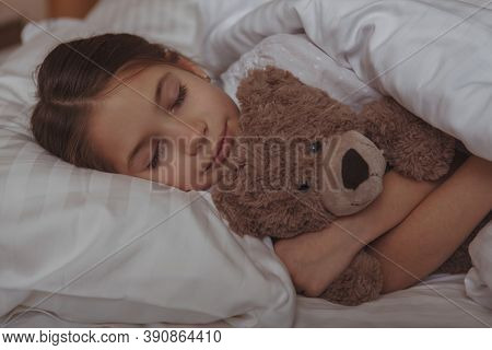 Close Up Of A Beautiful Little Girl Sleeping In Her Bed, Embracing Teddy Bear. Adorable Child Sleepi