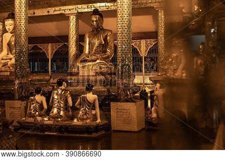 Yangon, Myanmar - December 30, 2019: Sitting Golden Buddha Statues Inside A Yellow Reflecting Room W