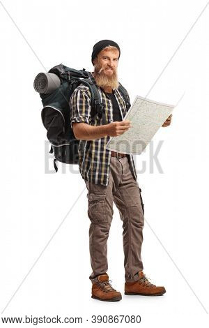 Full length shot of a bearded guy hiker with a backpack holding a map isolated on white background