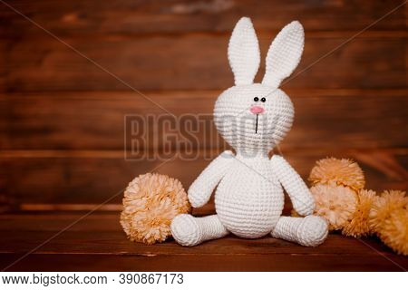 Handmade Amigurumi Rabbit On Wooden Background With Flowers. Baby Background. Copy Space