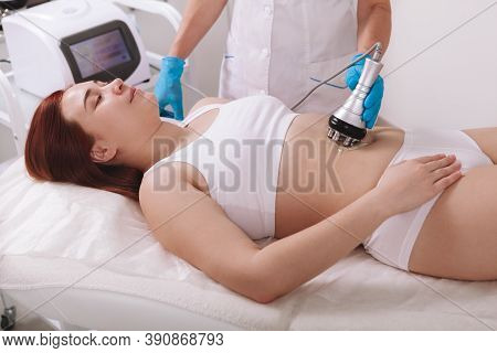 Young Woman Getting Rf-lifting Treatment By Cosmetologist At Beauty Salon. Weightloss, Fat Burning C