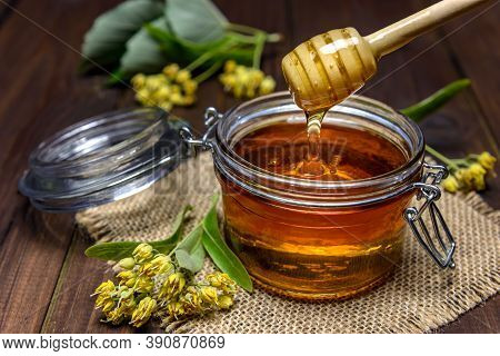 Linden Honey Is Pouring With Wooden Stick In A Jar Next To Linden Flowers. Selective Focus.