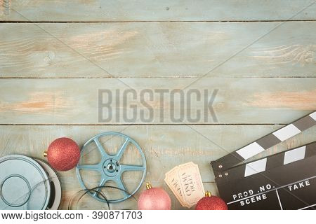 red christmas balls and cinema objects on wooden background