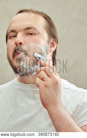 Portrait Of A 35-40 Year Old Man Shaving His Beard With A Razor, Close-up. Concept Of Self-cutting A