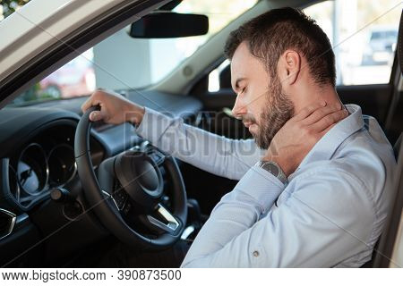 Young Man Rubbing His Aching Neck, Looking Tired From Driving. Male Driver Having Neck Pain, Sitting