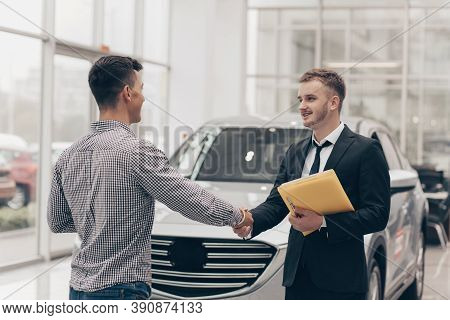 Professional Car Salesman Smiling, Shaking Hands With His Male Customer In Front Of A New Automobile