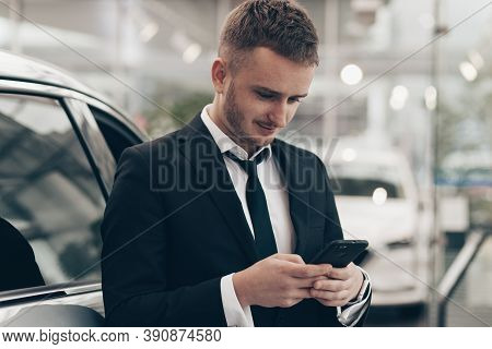 Businessman Using His Smart Phone At The Car Dealership. Young Salesman Working At Automobile Shop,