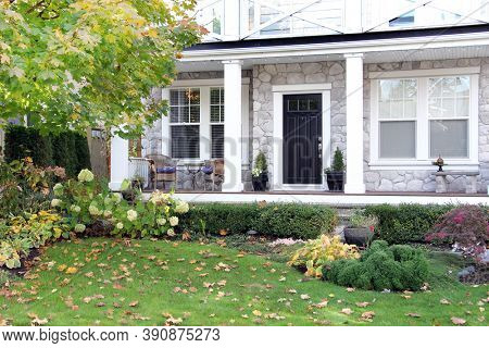 Front porch of a luxury home in Canada. Front yard of a beautiful new house in Autumn. Fall foliage in the garden.