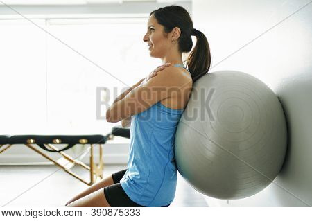 Young Woman Doing Exercise On Fitness Ball At The Physiotherapy Office