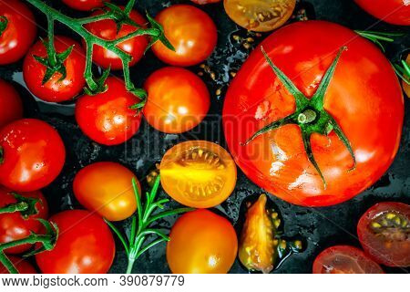 Variety of tomatoes, top view, over black.  Beef tomato, cherry tomatoes, roma and truss, whole and cut.