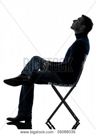 one causasian man sitting looking up   full length in silhouette studio isolated on white background