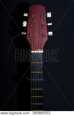 Guitar Head And Neck And Capo On A Black Background. Wooden Acoustic Six-string Guitar.
