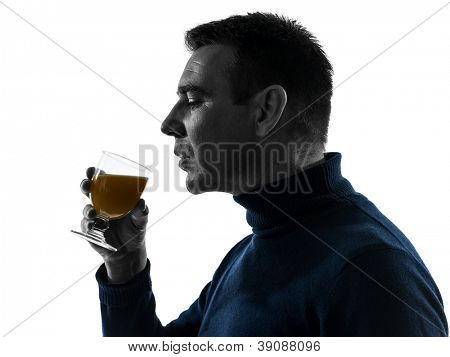 one causasian man drinking orange juice  portrait in silhouette studio isolated on white background