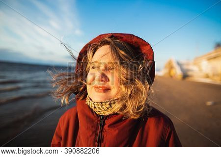 Beautiful Girl With Wild Hair In Hood Looking To The Sunset On The Sea Coast. Sunny Winter Day On Th