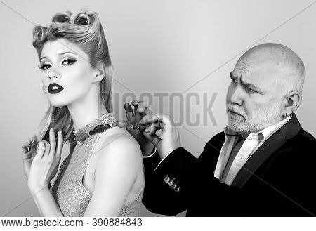 Couple Of Younger Woman And Elder Man Isolated At Orange Background. Crafty Blonde Woman Want To Mar