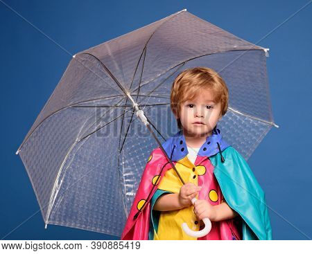 Smiling Little Boy Playing With Leaves And Looking At Camera. Cheerful Boy In Raincoat With Colorful